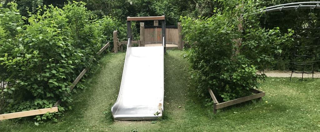 Toboggan dans une aire de jeux entouré de pelouse hybride